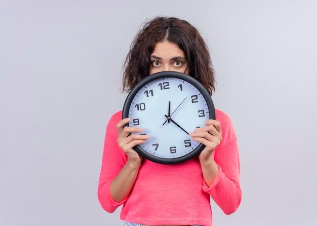 Giovane bella donna sorpresa che tiene orologio e nascondersi dietro di esso sulla parete bianca isolata con lo spazio della copia