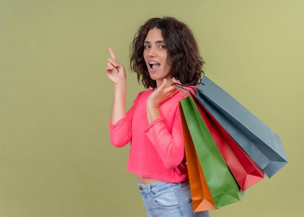 Giovane bella donna sorpresa che tiene i sacchetti di carta e che indica verso l'alto sulla parete verde isolata con lo spazio della copia