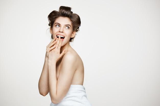 開いた口を浮かべてヘアカーラーで驚いたの若い美しい女性。美しさとスパのコンセプトです。