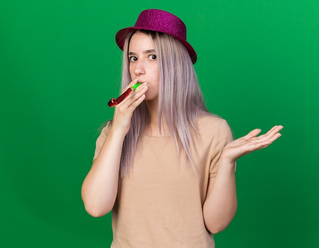 緑の壁に分離された手を広げてパーティーの笛を吹くパーティー帽子をかぶって驚いた若い美しい女性