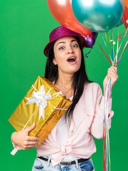 緑の壁に分離されたギフトボックスを保持している風船を保持しているパーティー帽子をかぶって驚いた若い美しい女性