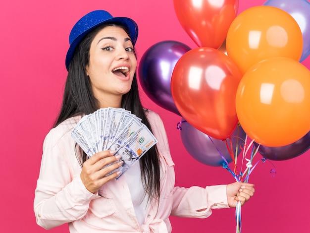 Sorpresa giovane bella donna che indossa un cappello da festa che tiene palloncini con contanti isolati su parete rosa