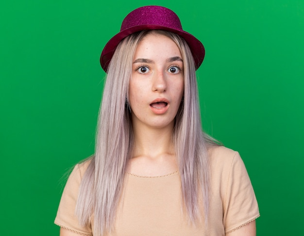 Surprised young beautiful woman wearing party hat isolated on green wall