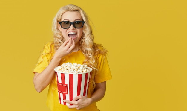 Surprised young blond woman in 3d glasses and yellow shirt eating popcorn, looks shocking movie at the cinema. isolated
