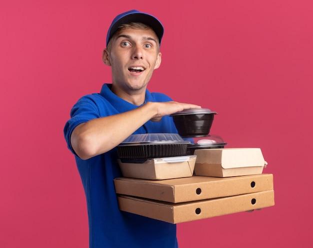 Удивленный молодой блондин посыльный, держащий пищевые контейнеры и пакеты на коробках для пиццы, изолированных на розовой стене с копией пространства