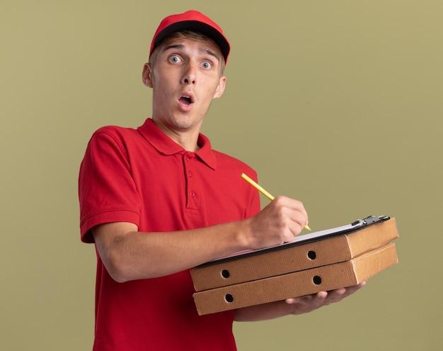 놀란 된 젊은 금발 배달 소년 올리브 그린에 피자 상자에 연필과 클립 보드를 보유