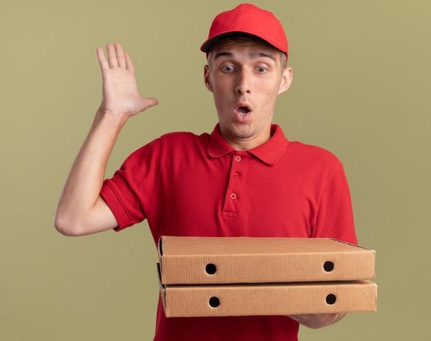 Удивленный молодой блондин посыльный стоит с поднятой рукой, держащей и смотрящими на коробки для пиццы, изолированные на оливково-зеленой стене с копией пространства