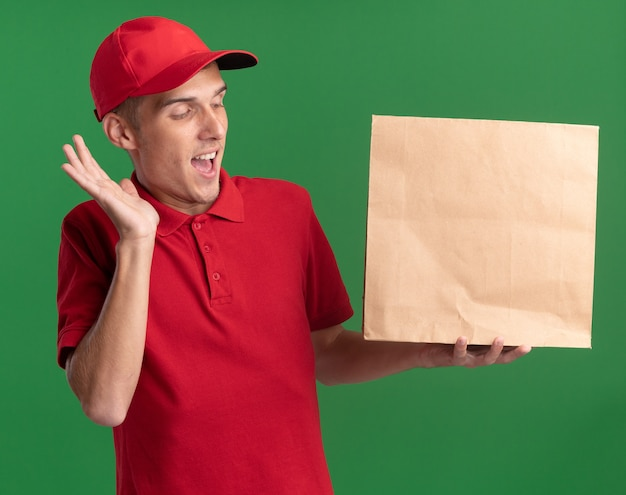 Surprised young blonde delivery boy stands with raised hand holding and looking at paper package isolated on green wall with copy space