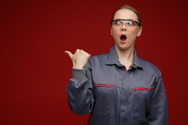 유니폼과 안전 안경을 찾고 측면을 가리키는 놀란 젊은 금발 여성 엔지니어