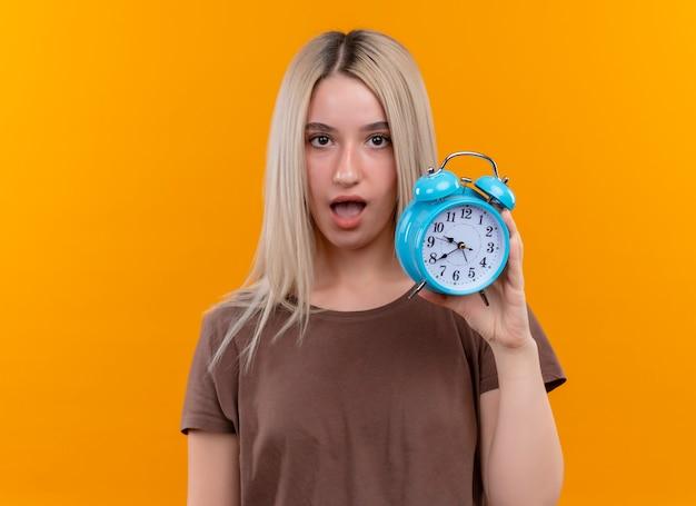 コピースペースと孤立したオレンジ色の壁に目覚まし時計を保持している驚いた若いブロンドの女の子