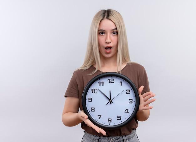 Giovane ragazza bionda sorpresa che tiene orologio sulla parete bianca isolata con lo spazio della copia