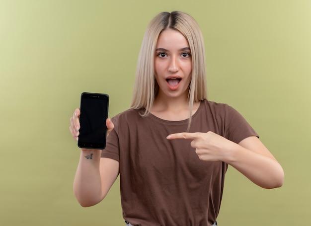 Giovane ragazza bionda sorpresa che tiene il telefono cellulare e indicandolo sulla parete verde isolata