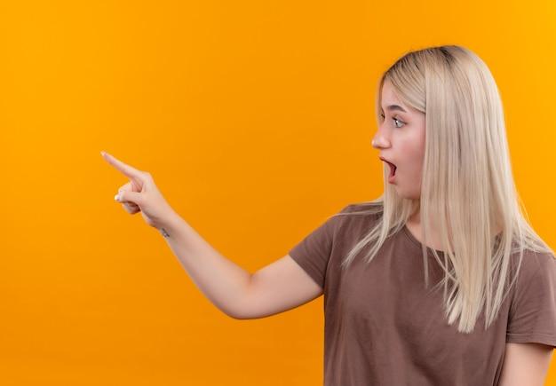 Удивленная молодая блондинка указывает и смотрит влево на изолированной оранжевой стене