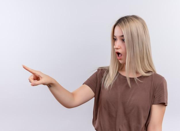Удивленная молодая блондинка указывая и глядя на левую сторону на изолированной белой стене