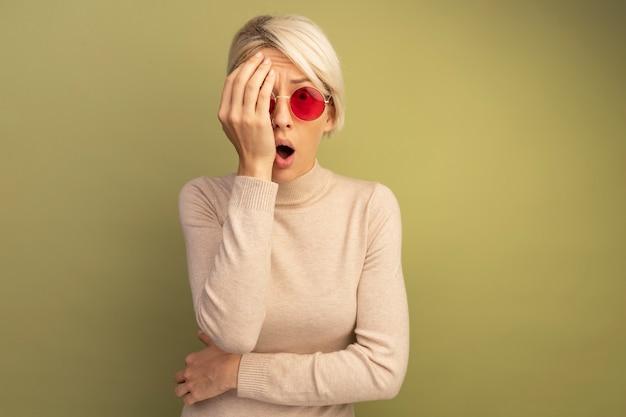 コピースペースのあるオリーブグリーンの壁に孤立して見える手で顔の半分を覆うサングラスを身に着けている驚いた若いブロンドの女の子