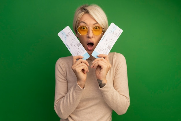Surprised young blonde girl wearing sunglasses holding airplane tickets near face  isolated on green wall with copy space