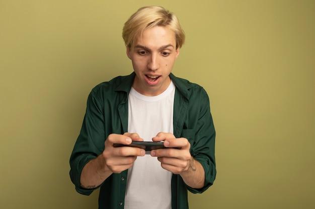 전화에서 재생 녹색 티셔츠를 입고 놀란 된 젊은 금발의 남자