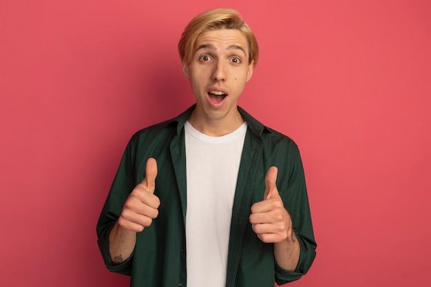親指を立てて緑のtシャツを着て驚いた若いブロンドの男