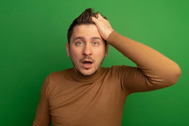 녹색 벽에 고립 된 전면을보고 머리에 손을 넣어 놀된 젊은 금발의 잘 생긴 남자