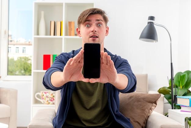 驚いた若い金髪のハンサムな男は、両手で電話を保持している肘掛け椅子に座っています