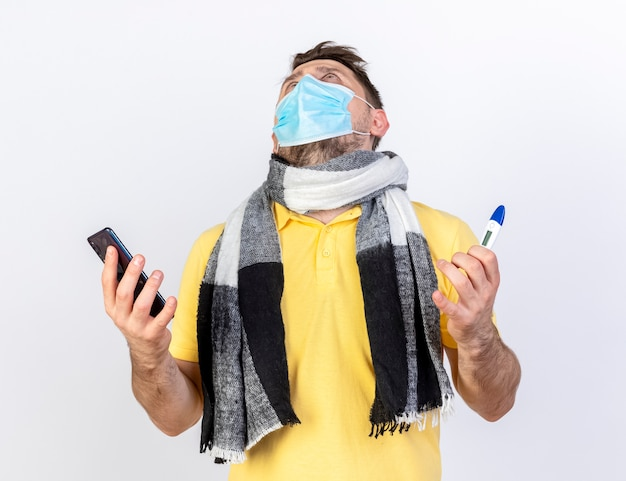 Surprised young blonde ill man wearing medical mask and scarf holds phone and thermometer isolated on white wall