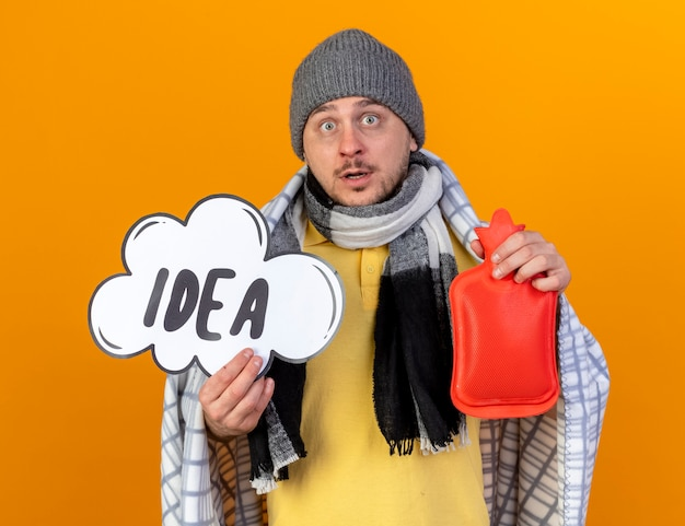 Surprised young blonde ill slavic man wearing winter hat and scarf wrapped in plaid holds idea bubble and hot water bottle isolated on orange wall with copy space