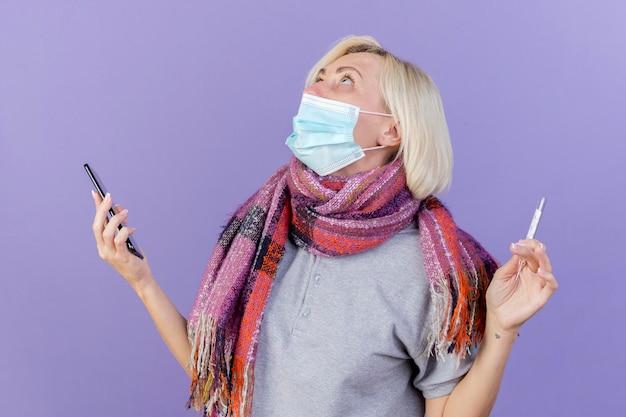 医療用マスクとスカーフを身に着けている驚いた若い金髪の病気のスラブ女性