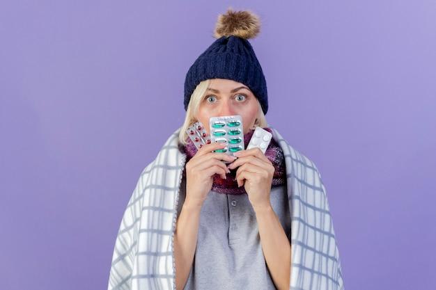 겨울 모자와 스카프를 입고 놀란 된 젊은 금발의 아픈 슬라브 여자