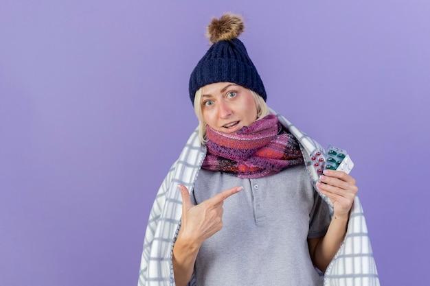 겨울 모자를 쓰고 놀란 된 젊은 금발 아픈 슬라브 여자