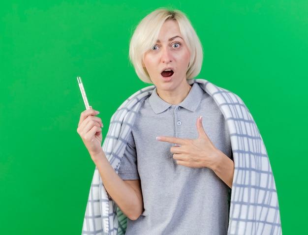 Giovane donna slava malata bionda sorpresa avvolta in prese di plaid e punti al termometro isolato sulla parete verde con lo spazio della copia