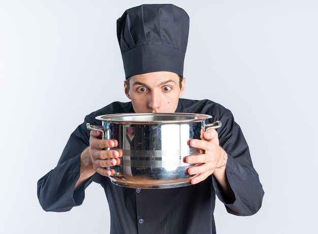 Surprised young blonde male cook in chef uniform and cap holding and looking at pot