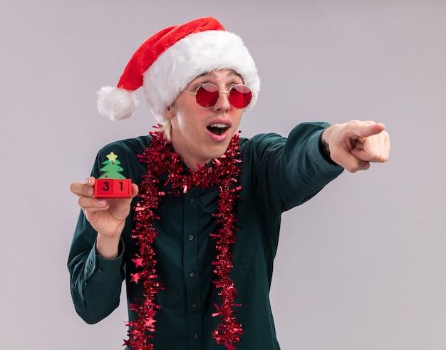 サンタの帽子と眼鏡をかけて、首の周りに見掛け倒しの花輪を身に着けている驚きの若いブロンドの男は、白い背景で隔離の側を見て、日付を指しているクリスマスツリーのおもちゃを保持しています