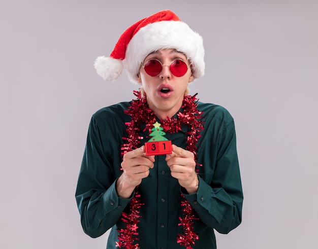 Surprised young blonde man wearing santa hat and glasses with tinsel garland around neck holding christmas tree toy with date looking at camera isolated on white background