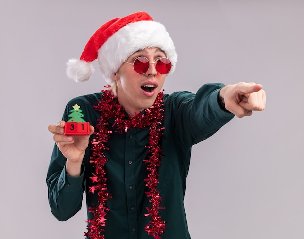 Surprised young blonde man wearing santa hat and glasses with tinsel garland around neck holding christmas tree toy with date looking and pointing at side isolated on white background