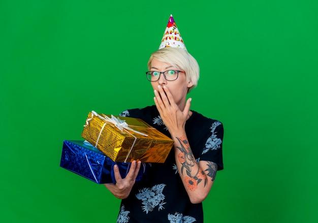 コピースペースと緑の背景で隔離の口に手を保つギフトボックスを保持している眼鏡と誕生日の帽子を身に着けている驚いた若いブロンドのパーティーの女の子