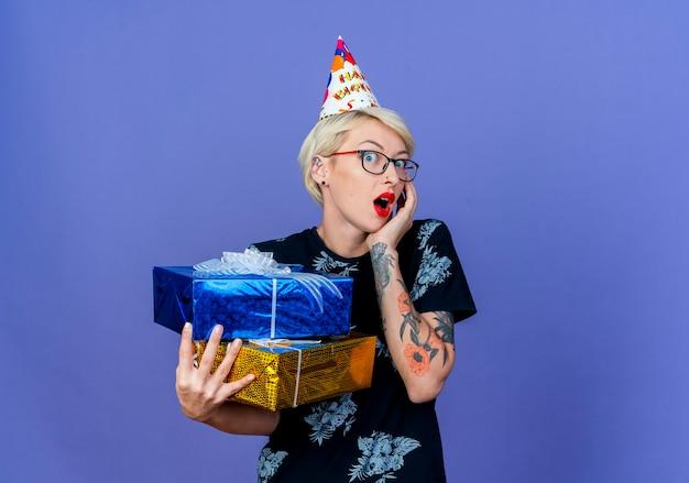 Удивленная молодая белокурая тусовщица в очках и кепке на день рождения держит подарочные коробки, глядя в камеру, держа руку на лице, изолированном на фиолетовом фоне с копией пространства