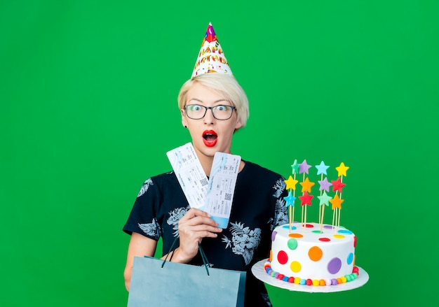 Surprised young blonde party girl wearing glasses and birthday cap holding birthday cake with stars airplane tickets and paper bag looking at camera isolated on green background with copy space
