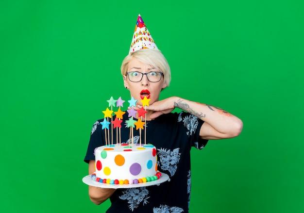 Ragazza bionda giovane sorpresa del partito con gli occhiali e berretto di compleanno che tiene la torta di compleanno con le stelle che tengono la mano sotto il mento che guarda l'obbiettivo isolato su priorità bassa verde con lo spazio della copia