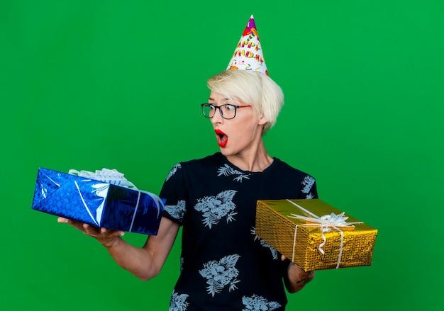 Giovane ragazza bionda sorpresa del partito con gli occhiali e cappello di compleanno che tengono i contenitori di regalo che esaminano uno di loro isolato su priorità bassa verde