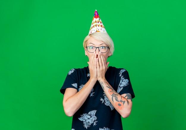 Giovane donna bionda sorpresa del partito che indossa occhiali e berretto di compleanno guardando la parte anteriore mantenendo le mani sulla bocca isolata sulla parete verde con lo spazio della copia