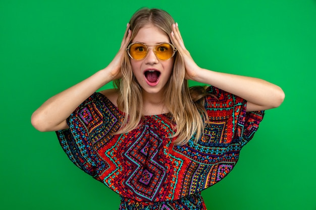 Surprised young blonde slavic girl with sun glasses putting hands on her head and looking at front