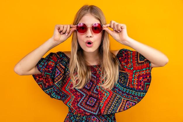 Giovane ragazza slava bionda sorpresa con gli occhiali da sole che esaminano la parte anteriore