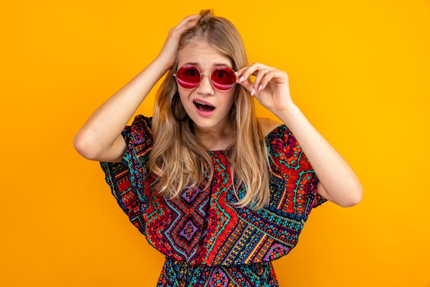彼女の頭に手を置いてサングラスをかけた驚いた若いブロンドのスラブの女の子と