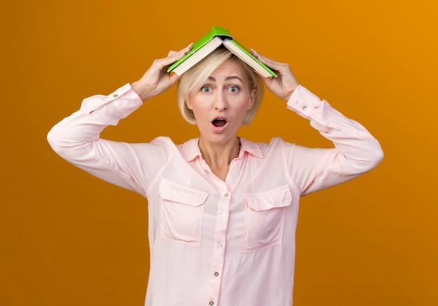 オレンジ色の壁に隔離された本で頭を覆った驚いた若い金髪のスラブ女性