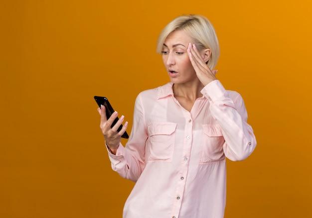 놀란 젊은 금발 슬라브 여자 잡고 전화를보고 오렌지에 고립 된 사원에 손을 넣어