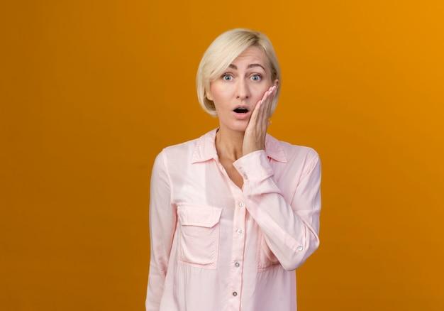 오렌지에 고립 된 뺨에 손을 넣어 놀란 된 젊은 금발 슬라브 여자