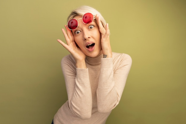 Giovane donna bionda sorpresa che alza gli occhiali da sole che guardano davanti isolato sulla parete verde oliva con lo spazio della copia