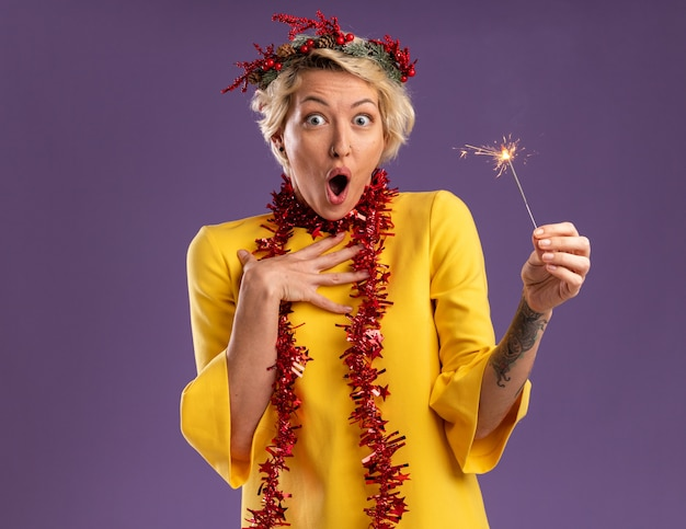 コピースペースで紫色の背景に分離されたカメラを見て胸に触れて休日線香花火を保持している首の周りにクリスマスのヘッドリースと見掛け倒しの花輪を身に着けている驚いた若いブロンドの女性