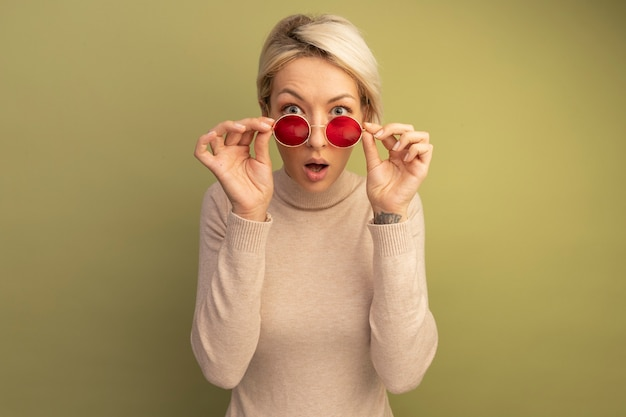 Sorpresa giovane donna bionda che indossa e afferra gli occhiali da sole guardando la parte anteriore isolata sulla parete verde oliva con spazio copia