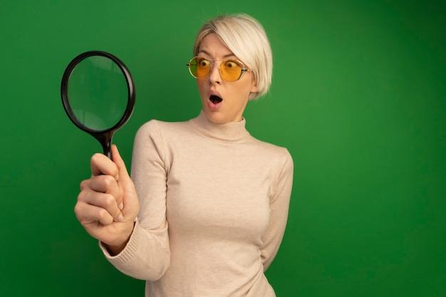 Удивленная молодая блондинка в солнцезащитных очках, держащая увеличительное стекло, смотрит в сторону сквозь нее, держа руку за спиной, изолированной на зеленой стене с копией пространства